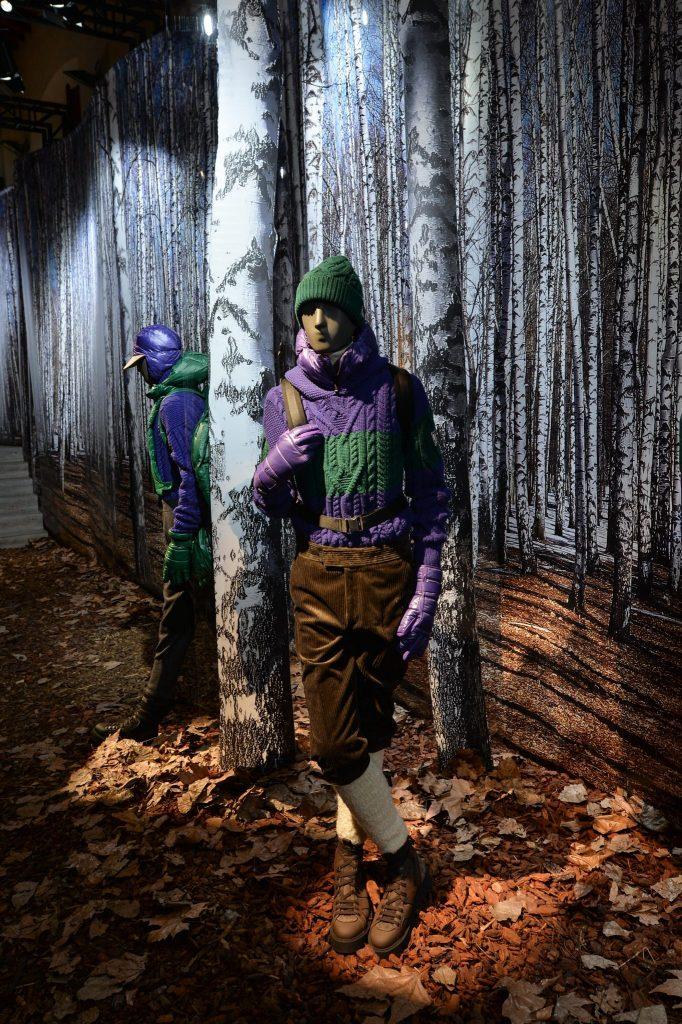 ZZegna Winter 2017. Shworoom in Waldkulisse mit Puppe in Kniebundhosen und grün-violettem Pullover mit Zopfmuster.