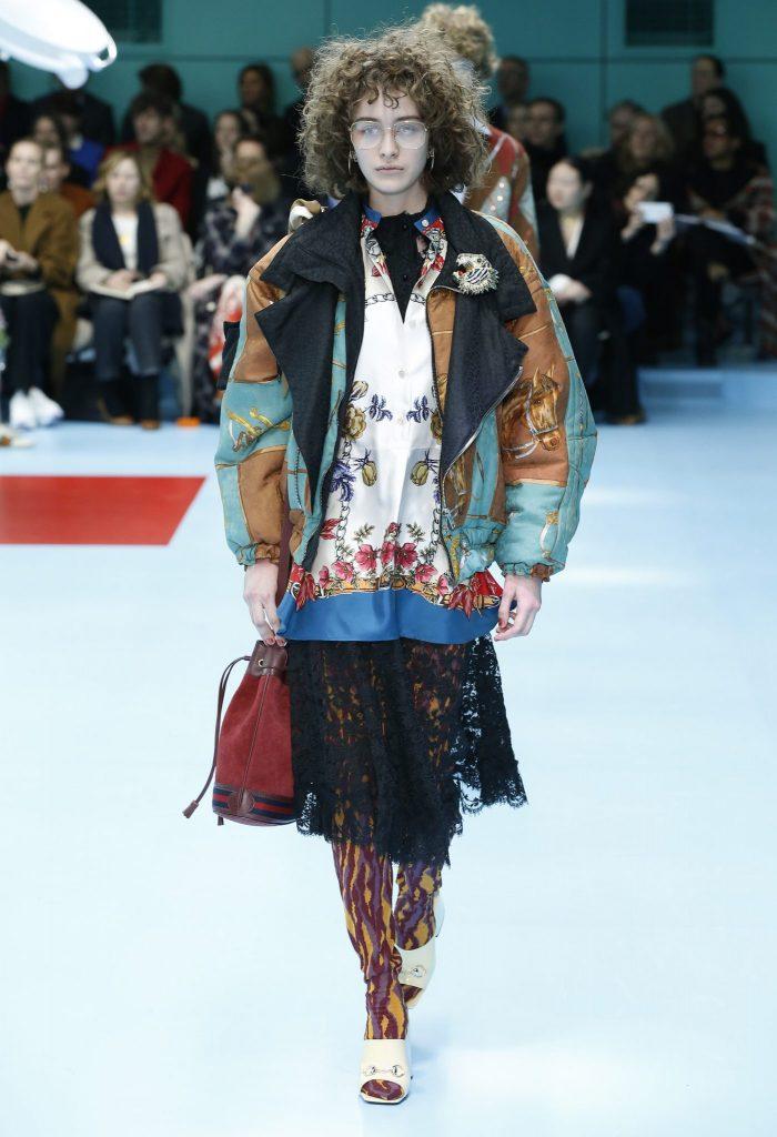 Gucci Schau Herbst/Winter 2018/19. Model mit oversized Jacke, Spitzenrock und weiter Bluse mit Blumendruck.